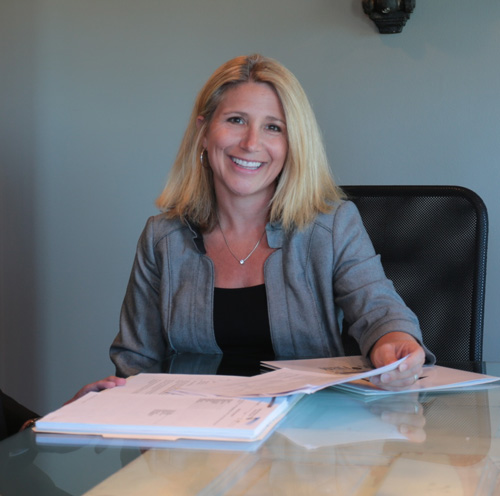 tracy Hirsch debt relief lawyer sitting at a desk with paperwork